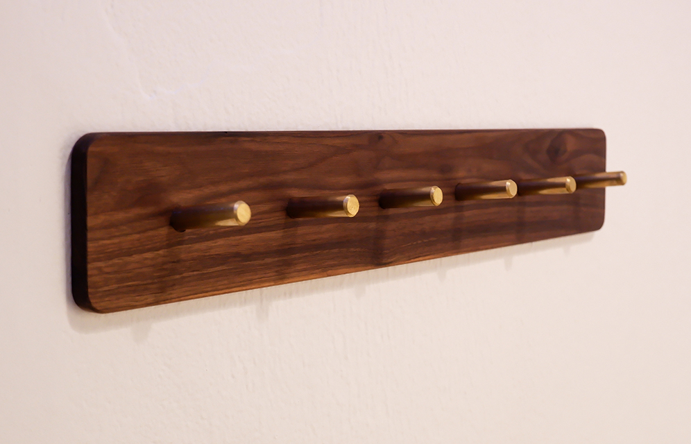 Wall kitchen rack made out of walnut and brass pins